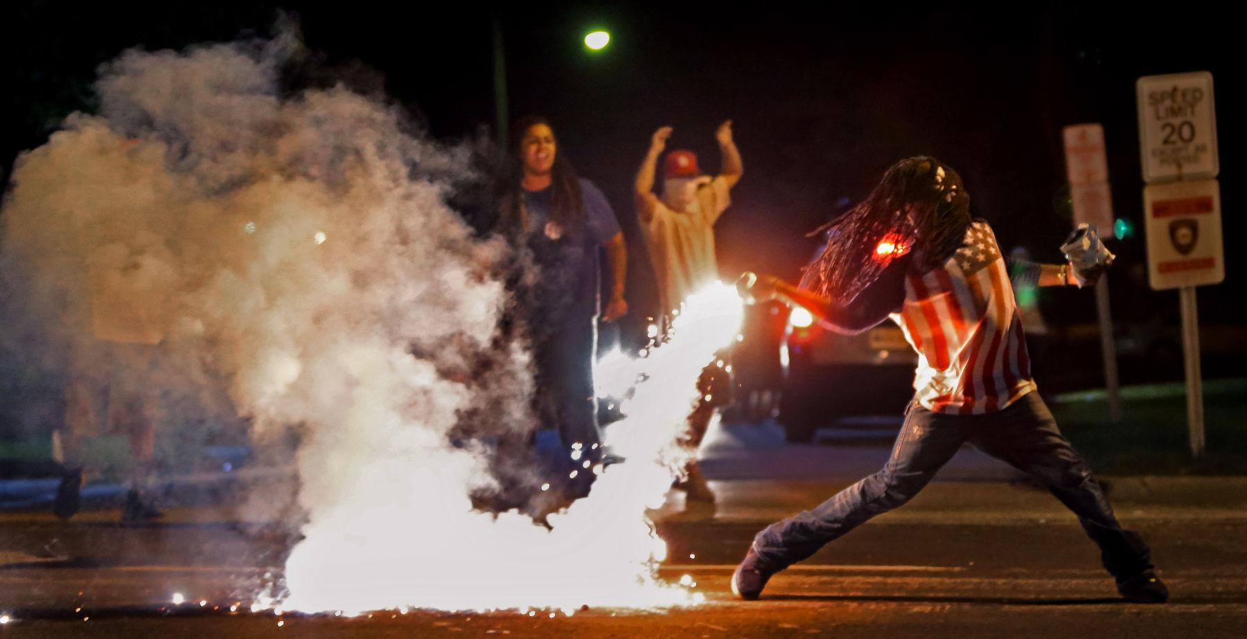 Edward Crawford, wearing an American flag T-shirt, picks up a smoking tear gas canister, and begins to throw it back toward police.