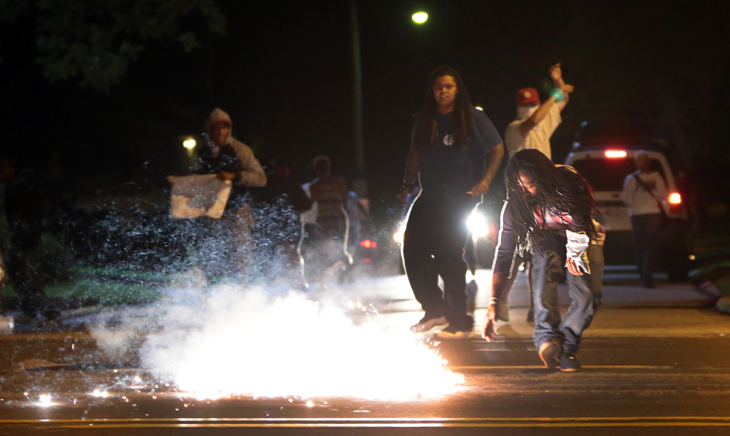 Edward Crawford reaches for the tear gas canister that has just landed nearby.