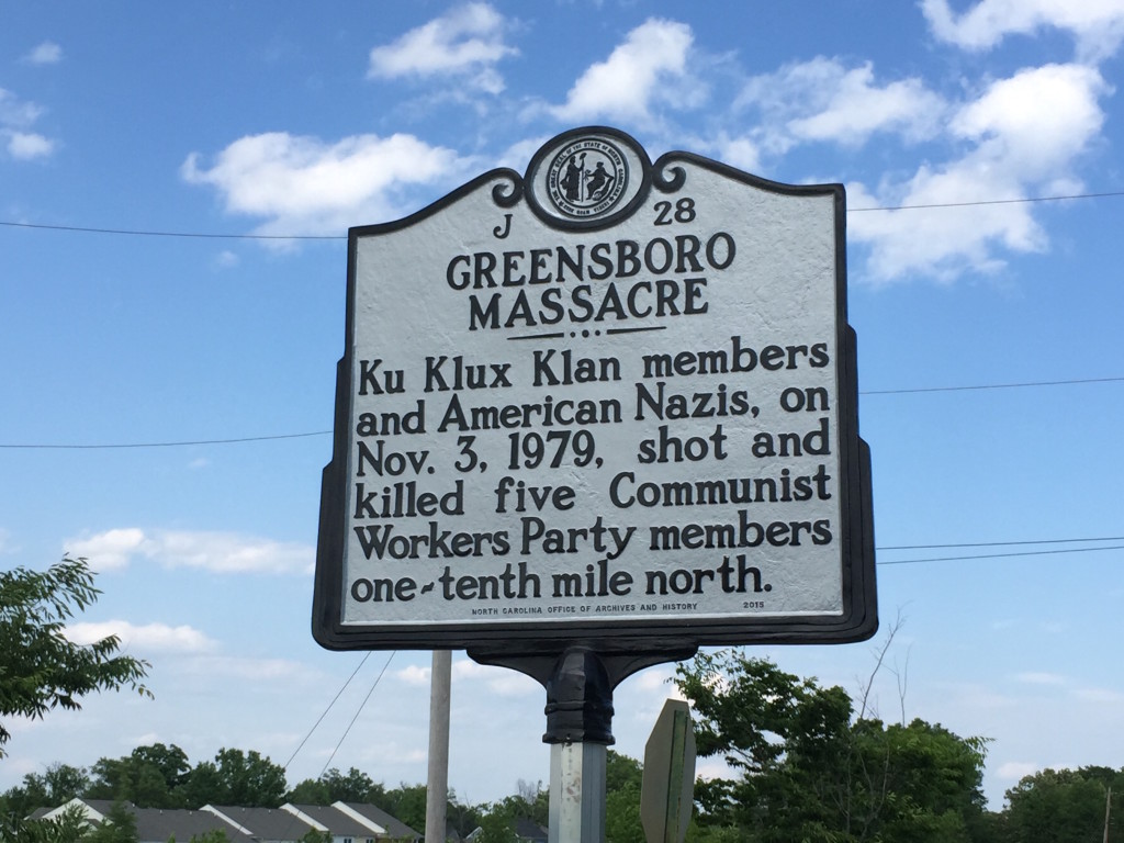 A memorial plaque for the Greensboro Massacre, reading: Ku Klux Klan members and American Nazis, on Nov. 3, 1979, shot and killed five Communist Workers Party members one-tenth mile north.