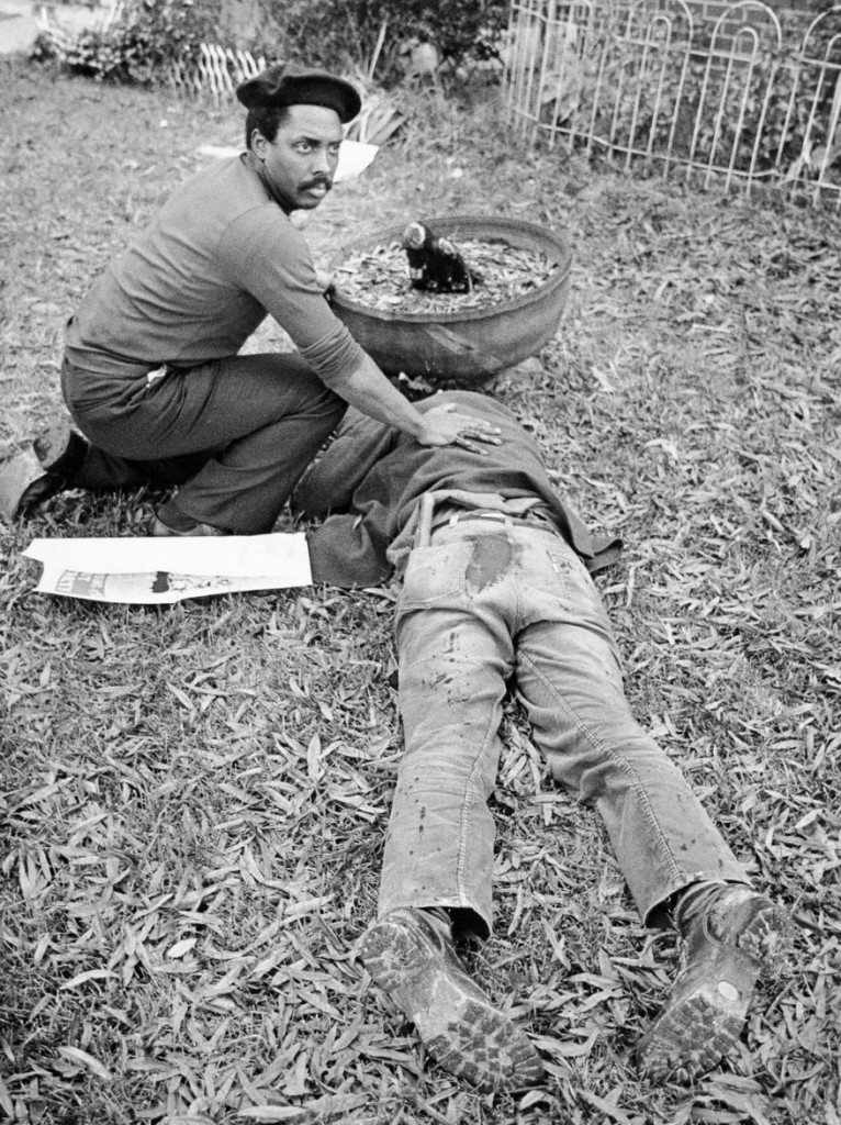 A Black man in a beret kneeling next to a facedown dead man's body, resting his hand on the dead man's back.