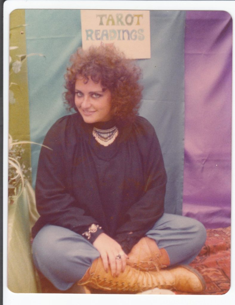 A photo of Meridy Volz as a young woman, beneath a hand-lettered Tarot Readings sign.