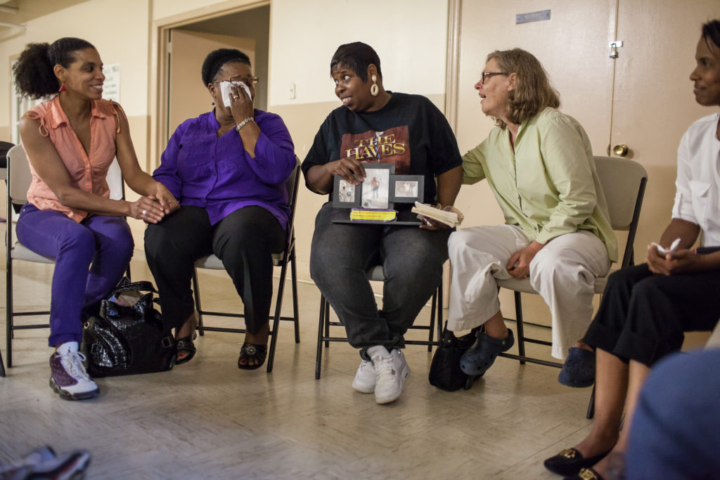 Mothers laugh and cry while talking about their children in the basement of The Shepherd's House United Methodist Church in Durham, NC.