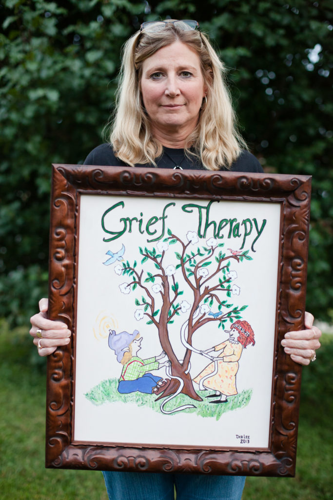 Frieda MacDonald holding up a piece of framed art that reads: Grief Therapy.