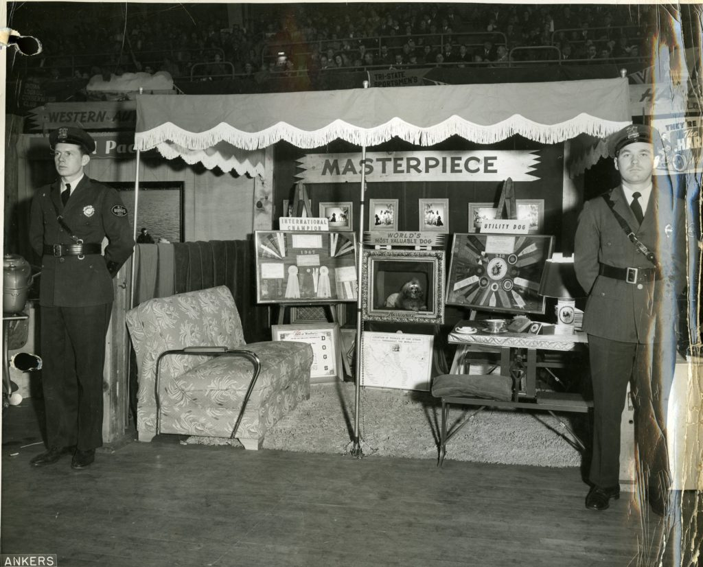Masterpiece surrounded by his awards, at a booth with guards flanking him on either side.
