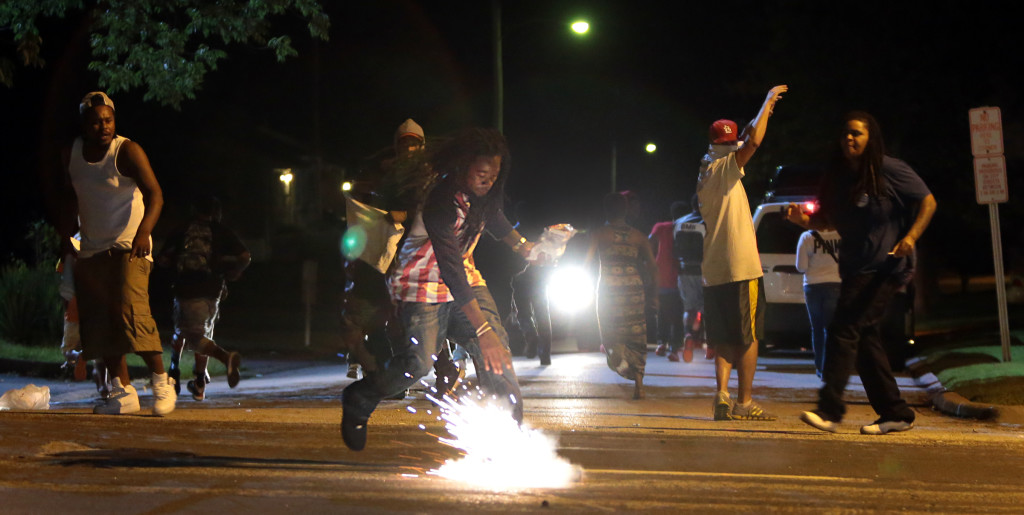 A tear gas canister lands at the feet of Edward Crawford.