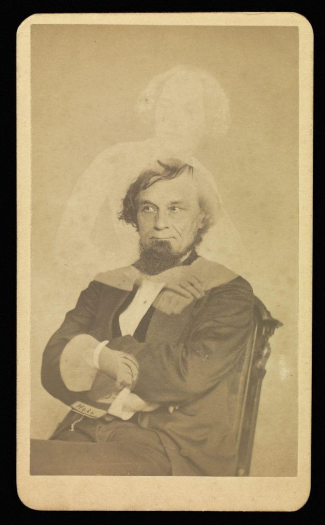 Sepia portrait photograph from the 1800s showing a man sitting in a chair, arms crossed, with a transparent woman standing behind him, arms appearing to be wrapped around the man.
