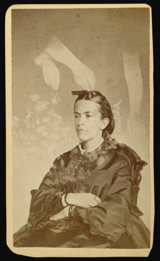 Sepia portrait photograph from the 1800s showing a woman sitting in a chair, angled and gazing beyond of the camera, with her arms crossed in her lap. Above her, three transparent arms place transparent flowers around the woman.