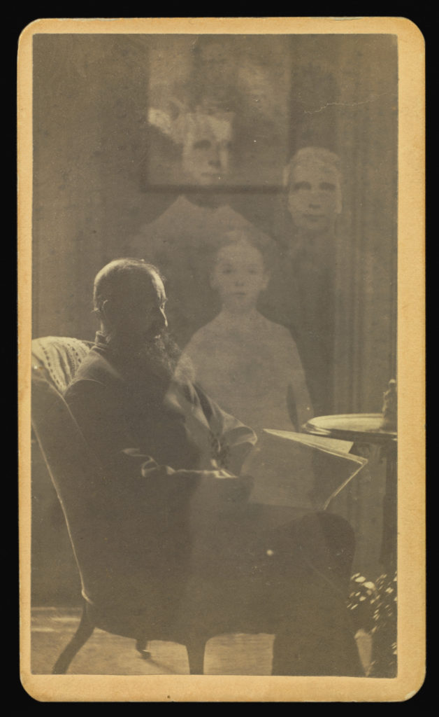 Sepia portrait photograph from the 1800s showing a man sitting in a chair reading a newspaper; next to him stand three transparent people.